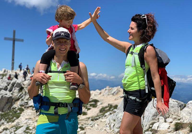 Trekking, famiglia felice in montagna con bambina nello zainetto - outdoorsoul.it