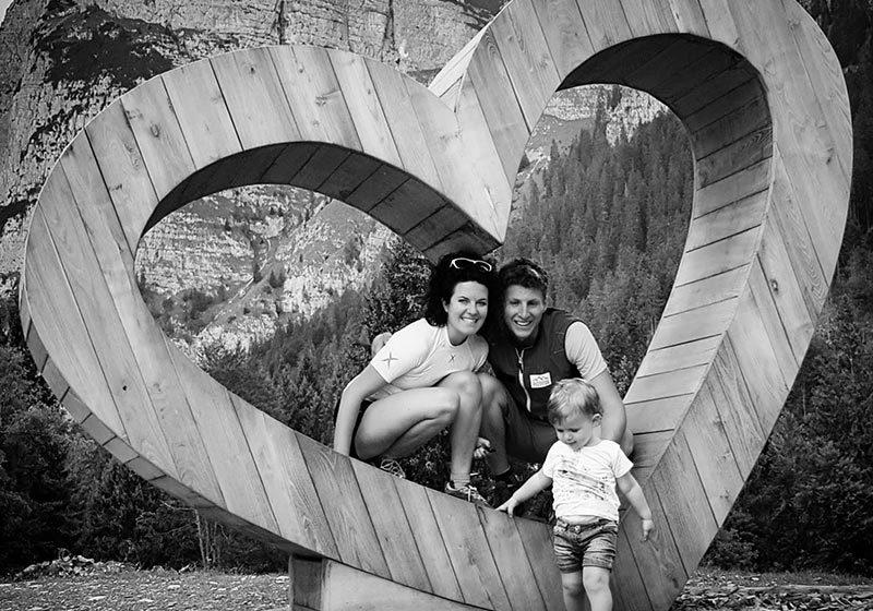 Trekking, famiglia felice con bambina all'interno di un cuore gigante di legno - outdoorsoul.it